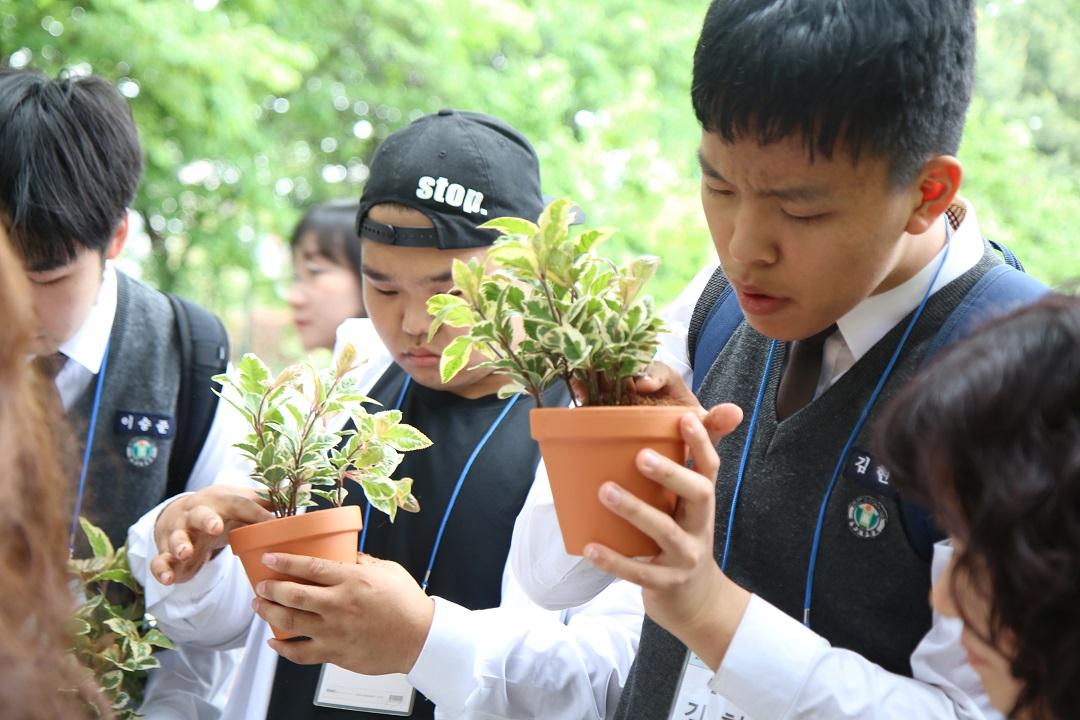 화분에 식물을 심고있는 학생사진