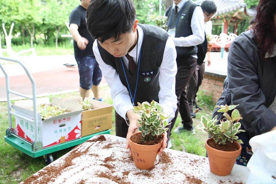 화분에 흙을 정리하고있는 학생사진