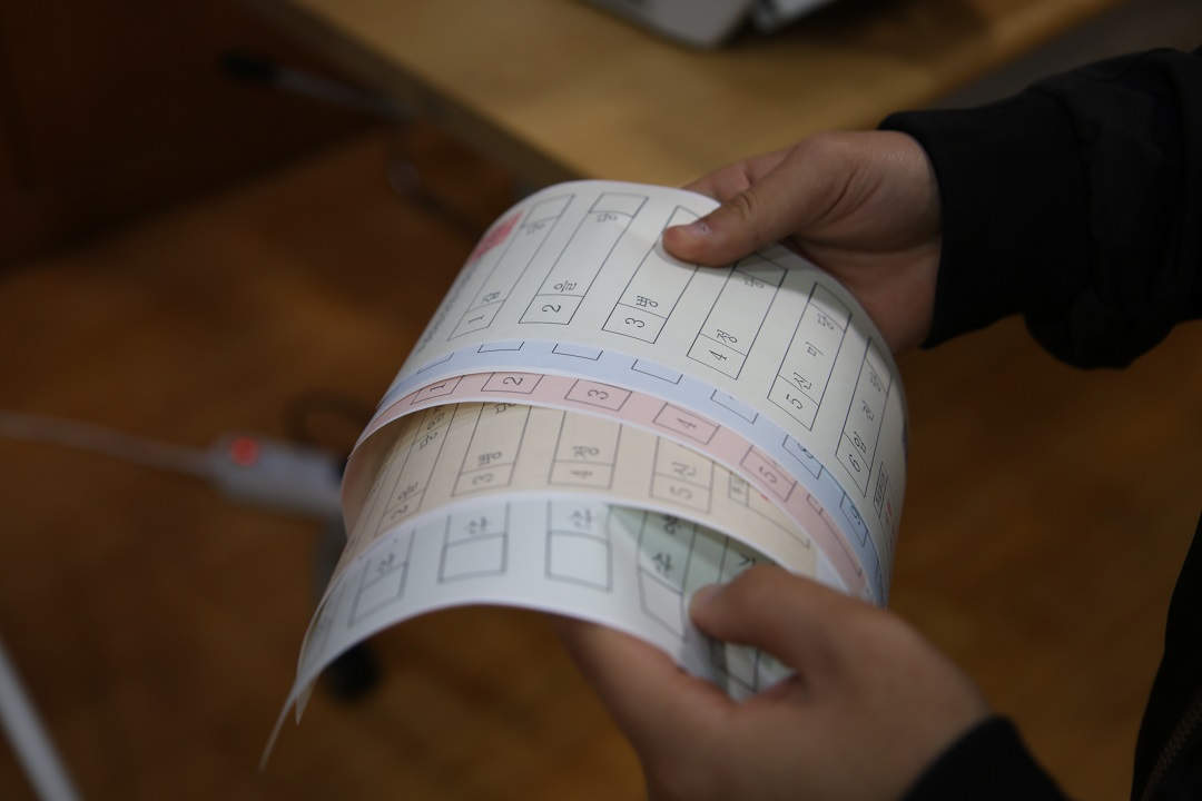 투표용지를 들고 있는 손의 모습