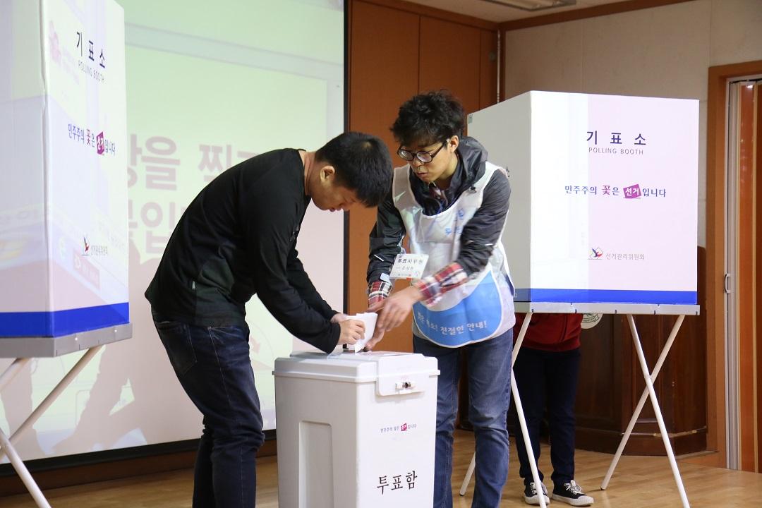 투표안내요원과 투표함에 투표용지를 넣는 모습